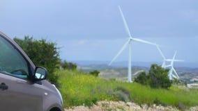 Ηλεκτρικό αυτοκίνητο, ανεμοστρόβιλοι που περιστρέφονται, πράσινη πηγή ενέργειας, καθαρό περιβάλλον φιλμ μικρού μήκους