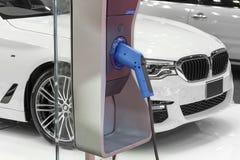 Ηλεκτρικό αυτοκίνητο που χρεώνει στο χώρο στάθμευσης με την ηλεκτρική χρέωση αυτοκινήτων Στοκ Εικόνες