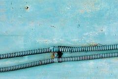 Ηλεκτρικό καλώδιο ενισχυμένη στη μέταλλο μάνικα ενάντια στο χρωματισμένο τοίχο στοκ φωτογραφία με δικαίωμα ελεύθερης χρήσης