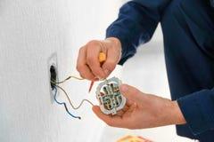 Ηλεκτρολόγος που συνδέει τα καλώδια με την υποδοχή στο νέο κτήριο, στοκ φωτογραφία