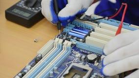 Ηλεκτρολόγος που χρησιμοποιεί το βολτόμετρο για τον εξοπλισμό γραφείων ελέγχου και επισκευής φιλμ μικρού μήκους