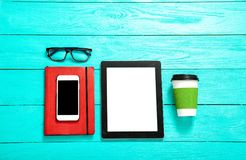 Ηλεκτρονικές συσκευές με την κενή οθόνη στο μπλε ξύλινο υπόβαθρο Φλιτζάνι του καφέ, γυαλιά και σημειωματάριο Εκλεκτική εστίαση Στοκ εικόνες με δικαίωμα ελεύθερης χρήσης