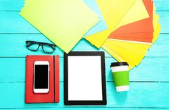 Ηλεκτρονικές συσκευές με την κενή οθόνη στο μπλε ξύλινο υπόβαθρο Εξαρτήματα φλιτζανιών του καφέ και εργασίας διάστημα αντιγράφων Στοκ Εικόνες