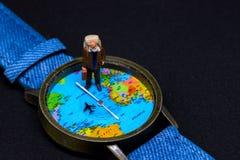 Ηληκιωμένος με τα ρολόγια χαρτών σακιδίων πλάτης και κόσμων Γύρω από το έμβλημα φωτογραφιών παγκόσμιου ταξιδιού Στοκ φωτογραφία με δικαίωμα ελεύθερης χρήσης