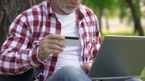 Ηληκιωμένος που πληρώνει για τις χρησιμότητες με την πιστωτική κάρτα, που χρησιμοποιεί το lap-top, συναλλαγή χρημάτων απόθεμα βίντεο