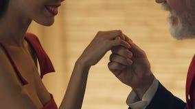 Ηληκιωμένος που φιλά το νέο χέρι γυναικών, πρώτη εξοικείωση στο ραντεβού στα τυφλά, ντροπαλή κυρία απόθεμα βίντεο