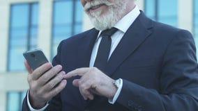 Ηληκιωμένος στο κοστούμι που χρησιμοποιεί το smartphone, τυλίγοντας τις φωτογραφίες στη χρονολόγηση app, ευτυχείς συγκινήσεις απόθεμα βίντεο