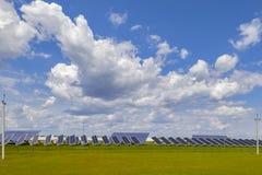 Ηλιακά πλαίσια εγκαταστάσεων παραγωγής ενέργειας σε έναν πράσινο τομέα κάτω από έναν μπλε ουρανό με τα χνουδωτά σύννεφα στοκ εικόνα με δικαίωμα ελεύθερης χρήσης