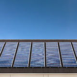 Ηλιακά πλαίσια σε μια σειρά σε μια στέγη με έναν μπλε ουρανό στοκ φωτογραφία
