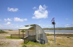 Ηλιακή τροφοδοτημένη ξηρά τουαλέτα λίπανσης Μπους φωτογραφιών αποθεμάτων με το πουλί Ν στοκ εικόνες