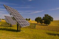 Ηλιακοί ιχνηλάτες και δέντρα στον οργωμένο τομέα στοκ εικόνες
