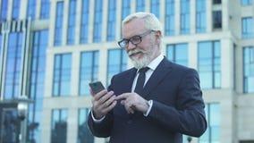 Ηλικίας αρσενικό στο formalwear να τυλίξει τηλέφωνο που στέκεται κοντά στις ειδήσεις κεντρικής ανάγνωσης γραφείων απόθεμα βίντεο