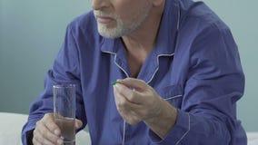 Ηλικίας αρσενικό χάπι εκμετάλλευσης σε ένα χέρι, ποτήρι του νερού σε άλλο, που αναστενάζει βαριά φιλμ μικρού μήκους