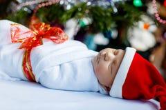 Ηλικίας νεογέννητο μωρό μιας εβδομάδας που τυλίγεται στο κάλυμμα κοντά στο χριστουγεννιάτικο δέντρο Στοκ Εικόνες