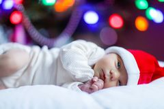 Ηλικίας νεογέννητο μωρό μιας εβδομάδας στο καπέλο Santa κοντά στο χριστουγεννιάτικο δέντρο Στοκ Εικόνες
