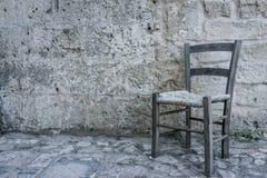Ηλικίας παλαιά παραδοσιακή καρέκλα στο κενό δωμάτιο πετρών στο αρχαίο φάντασμα Στοκ Εικόνες