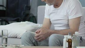 Ηλικίας συνεδρίαση ατόμων στο κρεβάτι, φάρμακα από την πλευρά, φέρνοντας αναπηρική καρέκλα νοσοκόμων στην πλάτη απόθεμα βίντεο