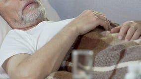 Ηλικίας ύπνος ατόμων στο κρεβάτι με το γυαλί που στέκεται στο μέτωπο, φάρμακα για την αϋπνία απόθεμα βίντεο