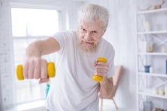 Ηλικιωμένα γενειοφόρα τρυπήματα άσκησης ατόμων με τους αλτήρες Στοκ Εικόνες