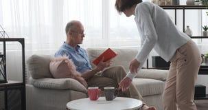 Ηλικιωμένα φλυτζάνια καφέ γυναικών φέρνοντας και ανάγνωση του βιβλίου με το σύζυγο στο σπίτι απόθεμα βίντεο