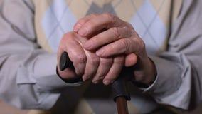 Ηλικιωμένα χέρια ατόμων που κρατούν το ραβδί περπατήματος, ανικανότητα, προβλήματα υγείας, κινηματογράφηση σε πρώτο πλάνο απόθεμα βίντεο