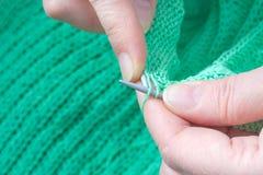 Ηλικιωμένα χέρια γυναικών που πλέκει ένα πράσινο πουλόβερ Στοκ Εικόνες