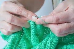 Ηλικιωμένα χέρια γυναικών που πλέκει ένα πράσινο πουλόβερ Στοκ φωτογραφίες με δικαίωμα ελεύθερης χρήσης