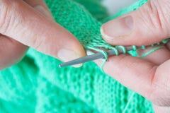 Ηλικιωμένα χέρια γυναικών που πλέκει ένα πράσινο πουλόβερ Στοκ Εικόνα