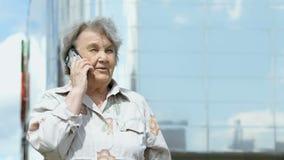Ηλικιωμένες συζητήσεις γυναικών που χρησιμοποιούν ένα έξυπνο τηλέφωνο υπαίθρια απόθεμα βίντεο