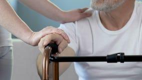 Ηλικιωμένη αρσενική συνεδρίαση με τα χέρια στο πλαίσιο περπατήματος, κυρία που βάζει τα χέρια στον ώμο απόθεμα βίντεο