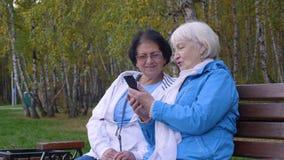 Ηλικιωμένη γυναίκα δύο που φαίνεται κινητό τηλέφωνο μαζί στο πάρκο πόλεων φθινοπώρου φιλμ μικρού μήκους