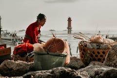 Ηλικιωμένη γυναίκα κατά να προετοιμάσει τα αγαθά πριν πέρα από το στενό Badung στοκ φωτογραφία