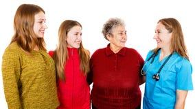 Ηλικιωμένη γυναίκα με τα granddaugthers και νέος γιατρός στοκ φωτογραφία