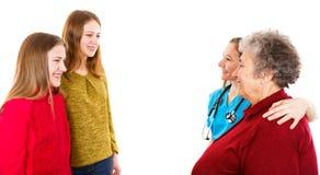 Ηλικιωμένη γυναίκα με τα granddaugthers και νέος γιατρός στοκ εικόνες με δικαίωμα ελεύθερης χρήσης