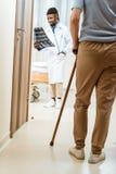 ηλικιωμένη γυναίκα με τον κάλαμο που περπατά σε ένα δωμάτιο νοσοκομείων με τη νέα εκμετάλλευση γιατρών στοκ φωτογραφία με δικαίωμα ελεύθερης χρήσης