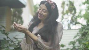 Ηλικιωμένη γυναίκα με το βατόμουρο στους φοίνικες απόθεμα βίντεο