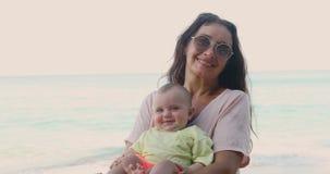 Ηλικιωμένη γυναίκα με το μωρό κοντά στη θάλασσα απόθεμα βίντεο