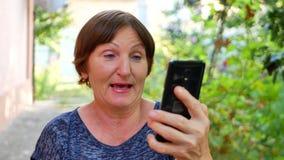 Ηλικιωμένη γυναίκα που έχει τη σε απευθείας σύνδεση τηλεοπτική συνομιλία που χρησιμοποιεί το μαύρο smartphone φιλμ μικρού μήκους