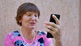 Ηλικιωμένη γυναίκα που έχει τη σε απευθείας σύνδεση τηλεοπτική συνομιλία που χρησιμοποιεί το μαύρο smartphone απόθεμα βίντεο