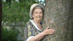 Ηλικιωμένη γυναίκα που αγκαλιάζει τα χαμόγελα δέντρων για τη κάμερα φιλμ μικρού μήκους