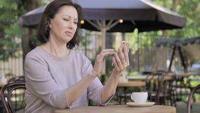 Ηλικιωμένη γυναίκα που ανατρέπεται από την απώλεια σε Smartphone, που κάθεται στον υπαίθριο καφέ απόθεμα βίντεο