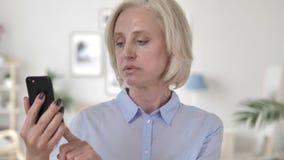 Ηλικιωμένη γυναίκα που ανατρέπεται από την απώλεια χρησιμοποιώντας Smartphone φιλμ μικρού μήκους