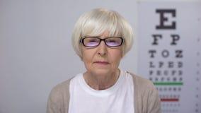 Ηλικιωμένη γυναίκα που ανατρέπεται με την εξέταση θέας που βγάζει τα θεάματα, κίνδυνος καταρρακτών απόθεμα βίντεο