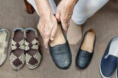 Ηλικιωμένη γυναίκα που βάζει στα παπούτσια στοκ εικόνα