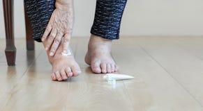 Ηλικιωμένη γυναίκα που βάζει την κρέμα στα πρησμένα πόδια στοκ φωτογραφίες με δικαίωμα ελεύθερης χρήσης