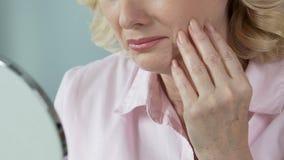 Ηλικιωμένη γυναίκα που εξετάζει τον καθρέφτη χεριών και που λυπάται για για τη χαμένη νεολαία, αποχώρηση απόθεμα βίντεο
