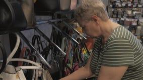 Ηλικιωμένη γυναίκα που επιλέγει την τσάντα στο κατάστημα απόθεμα βίντεο