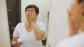 Ηλικιωμένη γυναίκα που εφαρμόζει την κρέμα προσώπου απόθεμα βίντεο