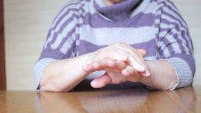 Ηλικιωμένη γυναίκα που εφαρμόζει την κρέμα χεριών απόθεμα βίντεο