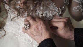 Ηλικιωμένη γυναίκα που κουμπώνει το γαμήλιο φόρεμα απόθεμα βίντεο